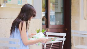 Young european woman with citymap in outdoors cafe. Portrait of attractive young tourist on lunch time stock video