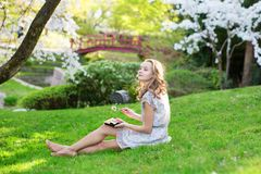 Young European woman eating sushi in Japanese park Stock Photo