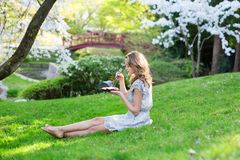 Young European woman eating sushi in Japanese park Royalty Free Stock Image