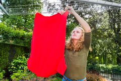 Young european woman hanging laundry at clothesline stock photo