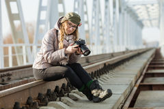 Young european woman photographer enjoying first spring sun exploring suburban locations railway bridge Royalty Free Stock Photo