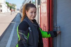 Young European woman portrait while entering train on rail road station, dressed motorcycle jacket Stock Images