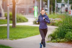 Young woman running in the morning in city park Stock Photography