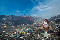 Young european woman sitting among trash at the garbage dump with truck  passing by Stock Photography