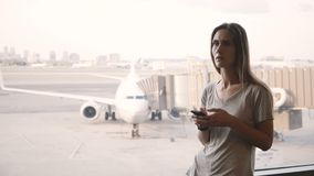 Young European woman standing near airport terminal window gets upset and frustrated looking at phone and smart watch. Girl is late and missing cancelled stock video