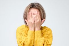 Young european woman in yellow sweater hides her face. Studio photo isolated on gray background. She has social phobia, tying to be anonym royalty free stock image