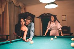 Young european woman look at couple playing billiard. She jelaous. Model is insane. Young man help asian woman to play game. Young european women look at couple royalty free stock photo