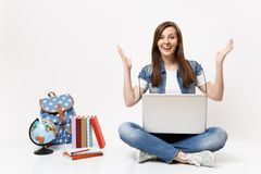 Young excited amazed woman student holding laptop pc computer and spreading hands sitting near globe, backpack, school. Books isolated on white background royalty free stock photography
