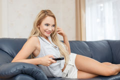 Young excited blonde woman watching TV Stock Images