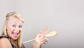 Excited cooking woman pointing to copyspace. Young, excited caucasian woman gesturing copy space with a wooden spoon in hand Royalty Free Stock Photos