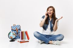 Young excited concerned woman student talking on mobile phone, spreading hands and sitting near globe, backpack, school stock photography
