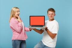 Young excited couple two friends guy girl in white pink t-shirts posing isolated on pastel blue background. People