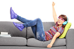 Young excited female listening music seated on a couch Royalty Free Stock Images