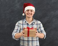 Young excited man in Santa hat with gift Royalty Free Stock Image