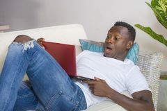 Young excited and surprised young black African American man in disbelief and shock face expression networking with laptop. Computer lying at home living room royalty free stock photos