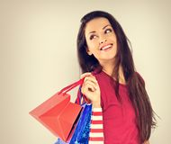 Young excited toothy smiling woman with shopping bags looking on toned vintage copy space background stock image