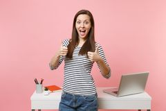 Young excited woman in casual clothes showing thumbs up work standing near white desk with laptop isolated on pastel. Pink background. Achievement business stock photo