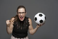 Young excited woman football fan holding soccer ball in hands stock photo