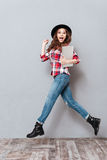 Young excited woman in hat holding laptop and jumping. Full length portrait of a young excited woman in hat holding laptop and jumping isolated over gray Royalty Free Stock Photography