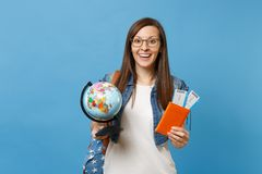 Young excited woman student in glasses with backpack holding world glove passport, boarding pass tickets isolated on. Blue background. Education in university stock photography