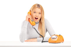 Young excited woman talking on a telephone stock photography