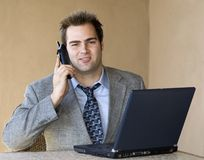 Young executive 2. Andsome young executive is using laptop and mobile phone Stock Photography
