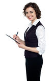 Young executive jotting down important notes. Pretty young corporate lady smiling at camera while writing on clipboard Stock Image