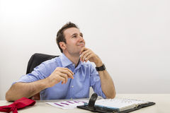 Young executive lost in happy thoughts. Young executive holding his chin on his hand and lost in happy thoughts at work Royalty Free Stock Photography