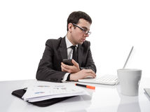 Young executive man working on laptop computer and holding a sma Royalty Free Stock Photo