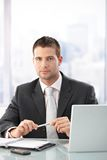 Young executive sitting in bright office Royalty Free Stock Photos