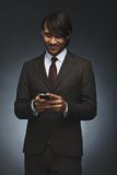 Young executive texting on his smart phone. Happy young executive texting on his smart phone. Handsome male associate reading test message on his cell phone Stock Images