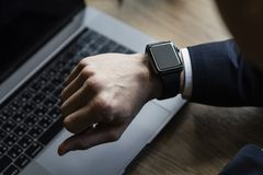 Mid section of male executive using smartwatch in office stock photos
