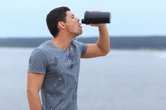 Young exhausted athlete drinking fresh water to refresh during a running trail. Stock Images