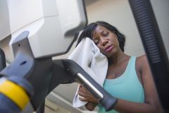 Young exhausted black afro American woman at fitness club drying sweat tired and sweaty training elliptical machine hard workout royalty free stock photography