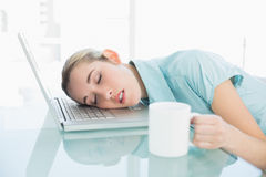 Young exhausted businesswoman sleeping sitting on her swivel chair Royalty Free Stock Photography