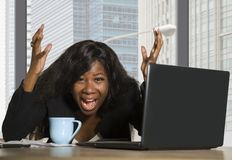Young exhausted and depressed black African American business woman working upset and sad at office computer desk by the window in. Central financial district royalty free stock photo