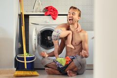Young exhausted husband father sitting in lotus pose near washing machine with pile of clothes and child on his lap. He can not stock photography