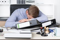 Young exhausted man is lying on the desk in office Stock Photos