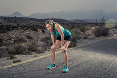 Young exhausted sport woman running outdoors on asphalt road breathing. Young exhausted sport woman running outdoors on asphalt road in mountain landscape and Royalty Free Stock Image