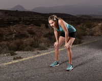 Young exhausted sport woman running outdoors on asphalt road stop for breathing tired Royalty Free Stock Photo