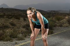 Young exhausted sport woman running outdoors on asphalt road stop for breathing tired Stock Photos