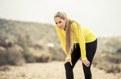 Young exhausted sport woman running outdoors on dirty road breathing Royalty Free Stock Photo