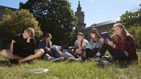 Young exhausted students learning on campus lawn. Group of tired, sleepy and exhausted college students preparing for exams on campus while sitting on green stock video footage