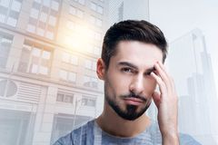 Young exhausted worker touching his head and feeling unwell. Feeling tired. Tired professional skilled worker touching his head while having a headache after a Royalty Free Stock Photography