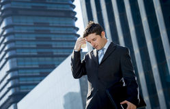 Young exhausted and worried businessman standing outdoors in stress and depression Stock Image