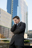 Young exhausted and worried businessman standing outdoors in stress and depression Royalty Free Stock Image