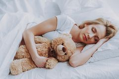 Young expectant woman sleeping in cozy bedroom. Happy pregnancy. Charming pregnant woman resting on bed at home while hugging teddy bear stock photos