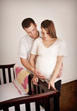 Young Expecting Parents standing by a crib Royalty Free Stock Photos