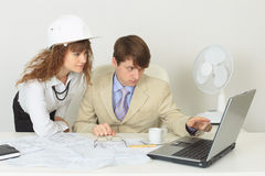 Young experts are occupied by work at office Royalty Free Stock Photos