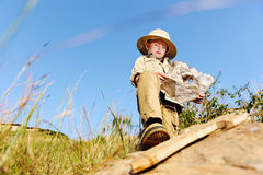 Young explorer. Young child playing pretend adventure explorer with wooden sword and treasure map royalty free stock image